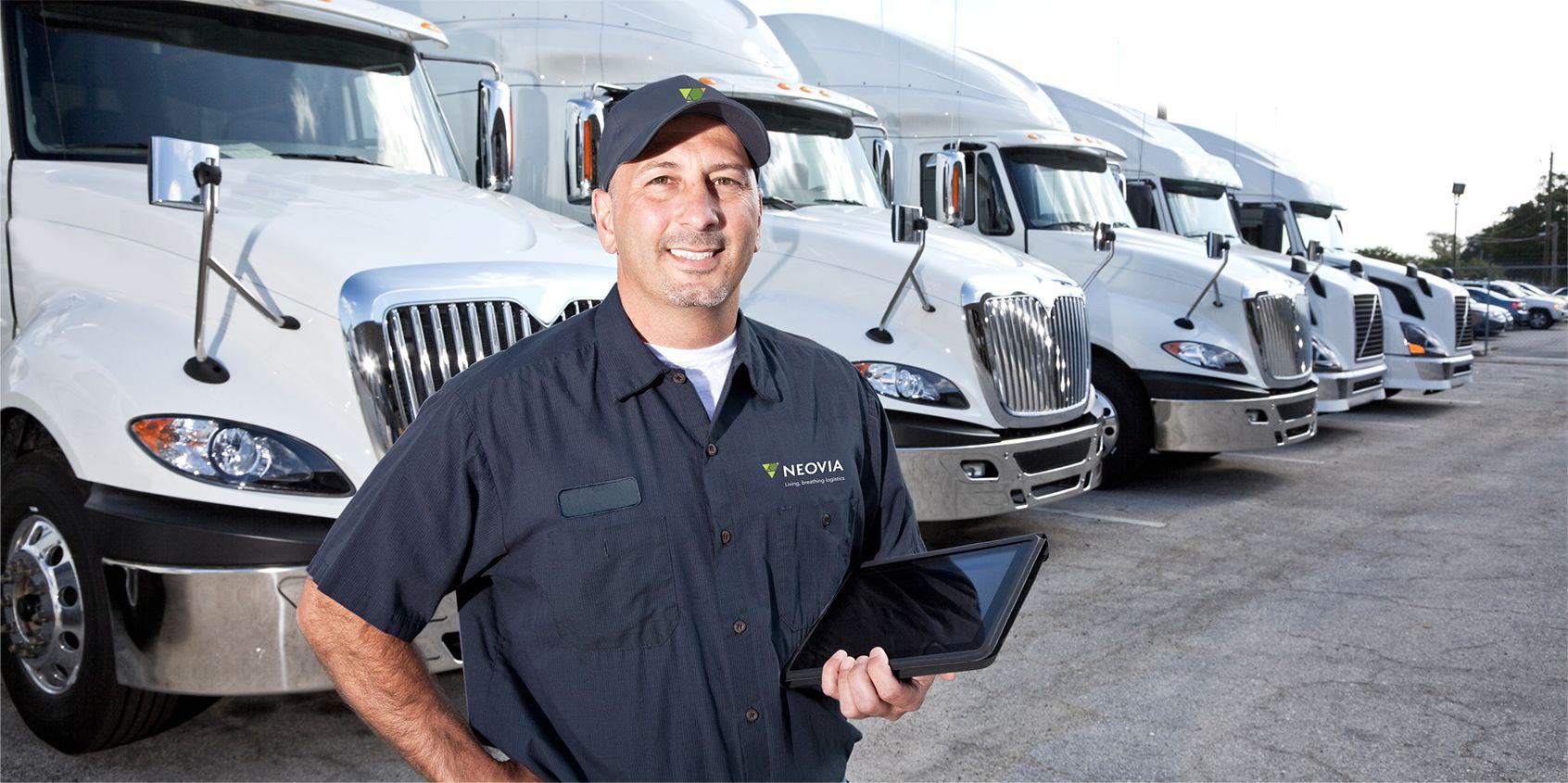 Neovia worker standing in front of row of semi trucks