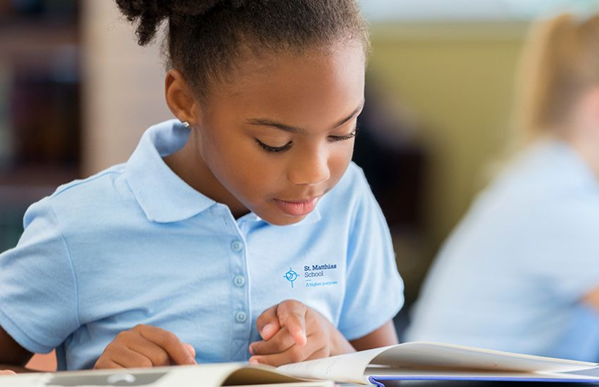 African American elementary school girl reading book at desk