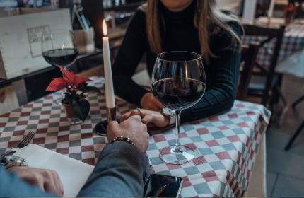 couple holding hands across table at dinner in restaurant