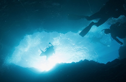 divers underwater in cave