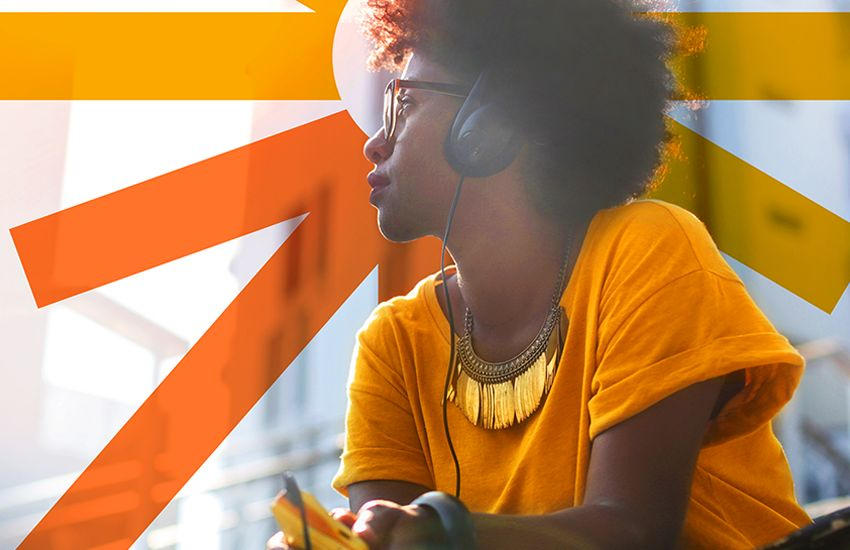 young African American woman in orange t-shirt with Ignite logo behind her